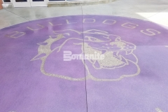 The Bomanite Exposed Aggregate Alloy System was used here to create a durable, decorative concrete hardscape with a custom purple color hardener and engraving at the center that adds a beautiful and distinctive quality to the exterior of this high school.