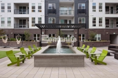 This beautiful gathering space at COLAB Co-Housing emits a modern, rustic elegance thanks to the stunning water feature that was created using board-formed decorative concrete and showcases an imprinted wood grain that enhances the relaxing atmosphere in this stylish student living community.